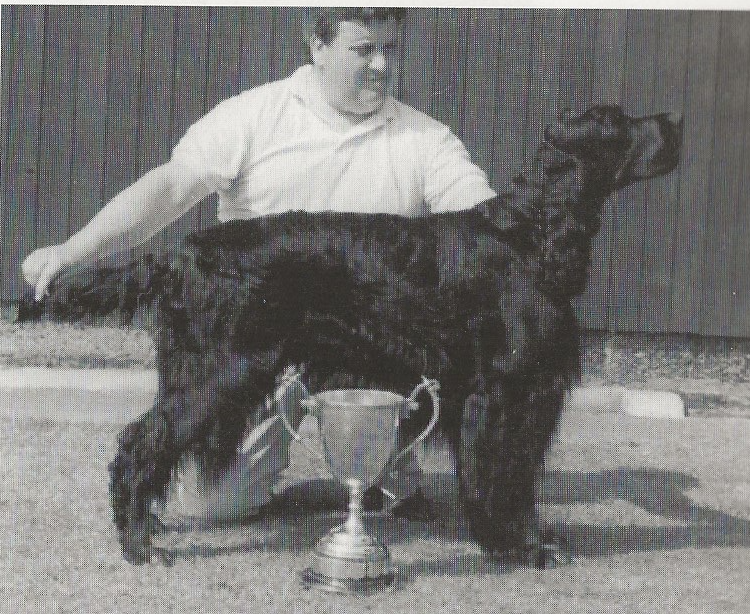 man with dog in front of silver trophy