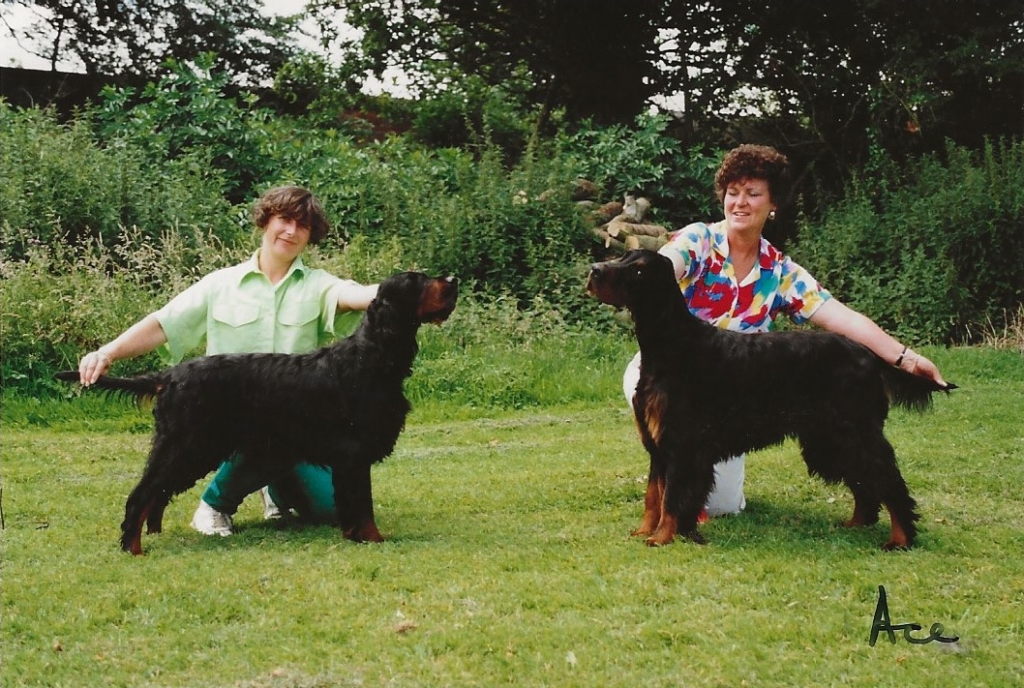 Two women posing black and tan dogs